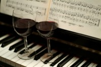 Two glasses of red wine on piano keys
